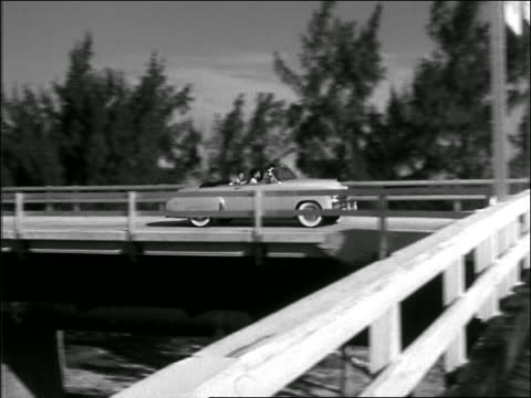 b/w 1949 pan family driving in convertible on bridge / florida - family convertible stock videos & royalty-free footage