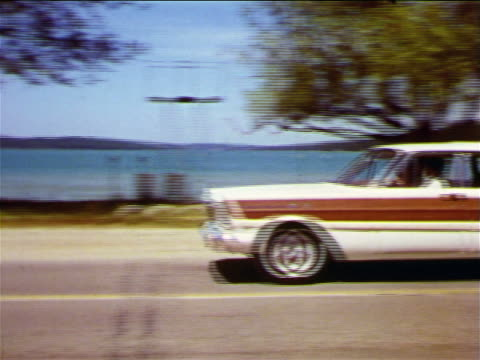 1965 pan family driving in ford station wagon past lake / industrial - ford motor company stock videos and b-roll footage