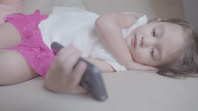 familie während covid-19 lockdown: kleines baby mädchen mit handy - begräbnis stock-videos und b-roll-filmmaterial