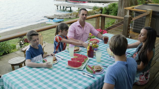 stockvideo's en b-roll-footage met family eating and sharing picnic food by lake connaught, washington, usa. - familie met drie kinderen