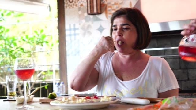 familie essen vorspeise essen vor dem grillen auf einem strandhaus in brasilien - brasilien stock-videos und b-roll-filmmaterial