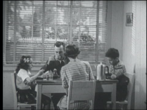 b/w 1950 family eating at breakfast table / father gets up + leaves as car pulls up in front - tapparella video stock e b–roll