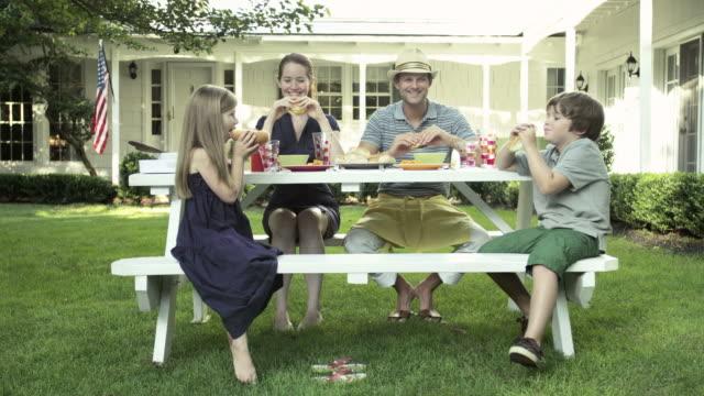 vidéos et rushes de family eating at picnic table - culture américaine