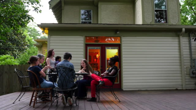 MS Family eating birthday cake together on backyard patio of home on summer evening