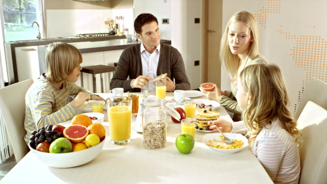 family eating breakfast at a nicely set table - dining table stock videos & royalty-free footage