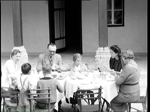 stockvideo's en b-roll-footage met 1937 b/w ws ha family eating breakfast on terrace / germany - 1937