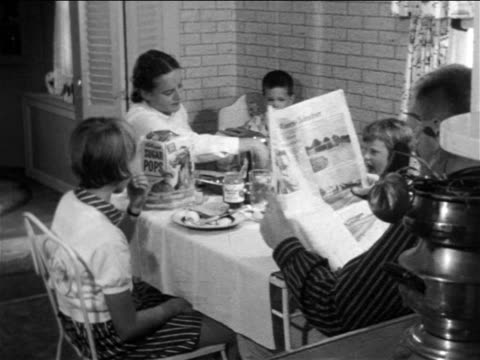 b/w 1957 family eating breakfast together at kitchen table / educational - breakfast stock videos & royalty-free footage