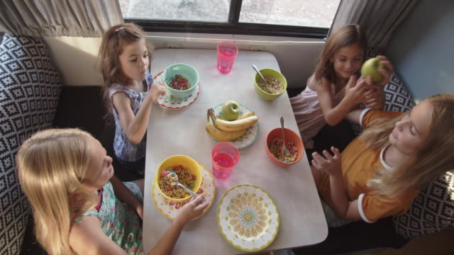 family eating breakfast together in an rv - tavolo video stock e b–roll