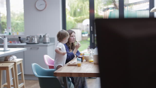 vídeos de stock, filmes e b-roll de family eating breakfast together - cereal