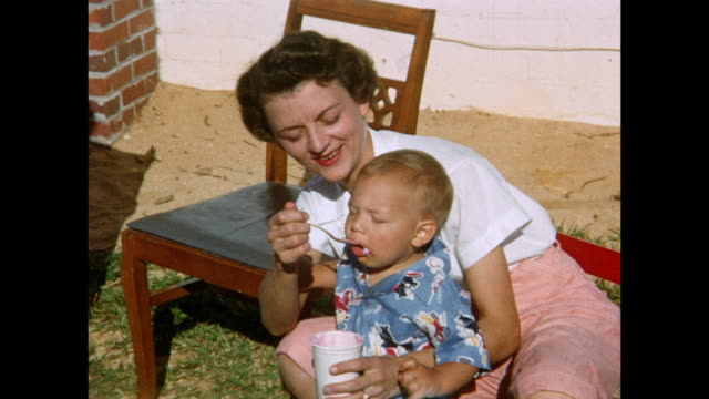 stockvideo's en b-roll-footage met 1954 home movie family eating cake and enjoying birthday party in backyard / daytona beach, florida  - 50 59 jaar