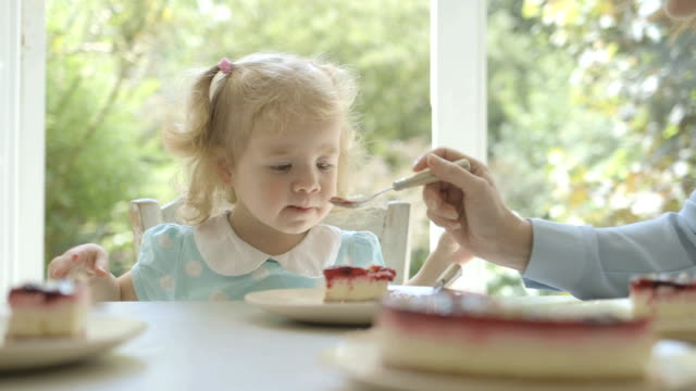 family eating cake with child in kitchen. - sharing stock videos & royalty-free footage