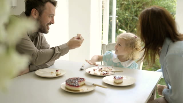 Family eating cake with child in kitchen.