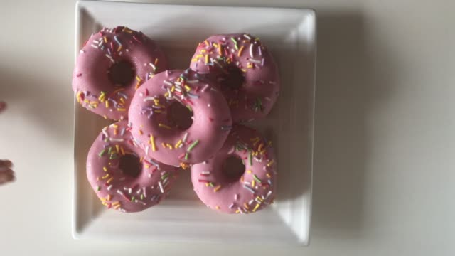 family eating four sweet pink glazed doughnuts - ungesunde ernährung stock-videos und b-roll-filmmaterial