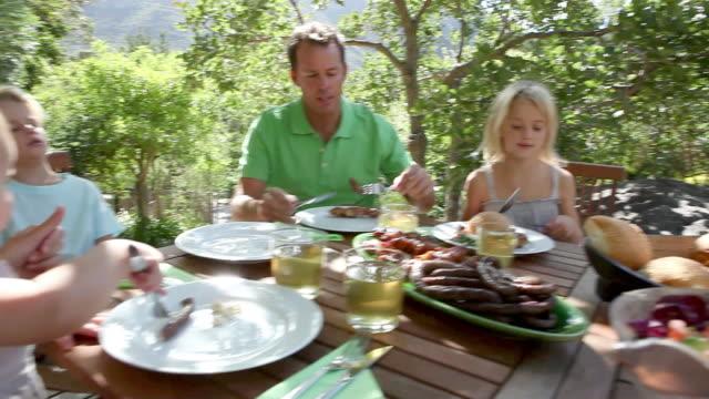 vídeos de stock e filmes b-roll de family eating lunch al fresco - almoço