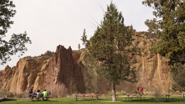 A family eating lunch at a table inside of Smith Rock State Park.