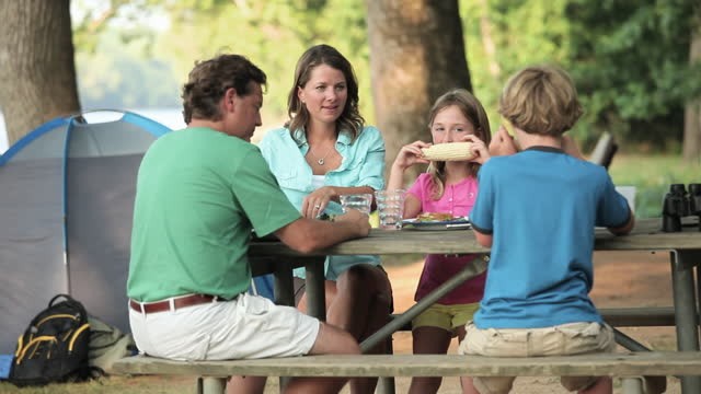 Family eating lunch at campsite picnic table