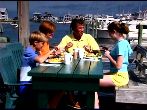 family eating meal at outdoors restaurant near marina - see other clips from this shoot 1335 stock videos and b-roll footage