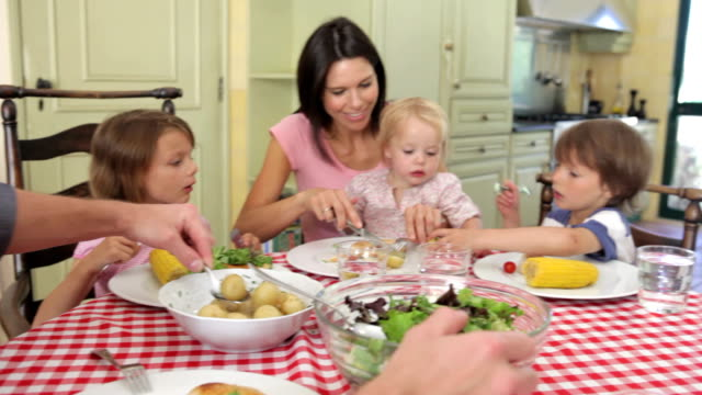 family eating meal together in kitchen - social grace stock videos & royalty-free footage