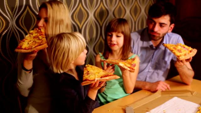 vídeos y material grabado en eventos de stock de familia comiendo una pizza en su casa - doughter