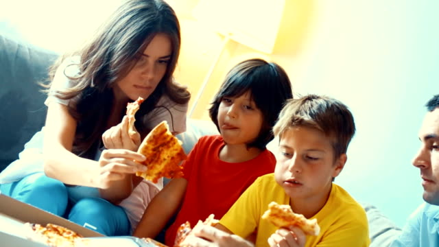 Family eating pizza at home.
