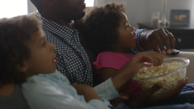 family eating popcorn and watching television - genderblend stock videos & royalty-free footage