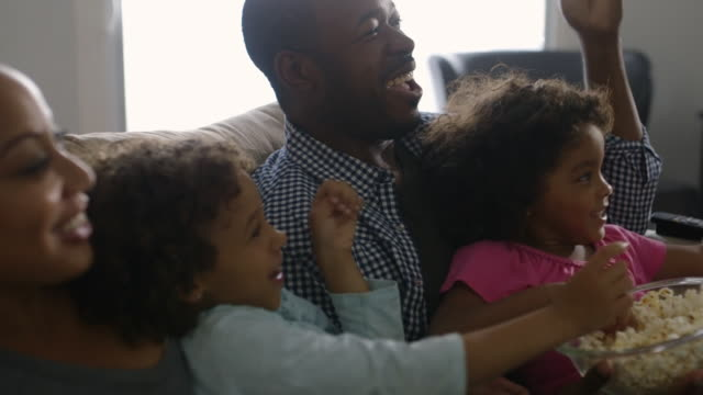 family eating popcorn and watching television - watching tv stock videos & royalty-free footage