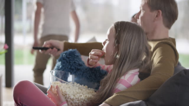 vídeos de stock e filmes b-roll de family eating popcorn and watching tv - controlo remoto