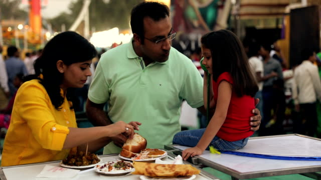 stockvideo's en b-roll-footage met family eating snacks at fair, delhi, india - voeren