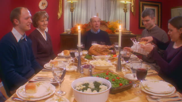 slo mo pan family eating thanksgiving meal - wealth stock videos & royalty-free footage
