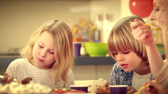 Familie essen Kuchen in der Geburtstag party-Tisch