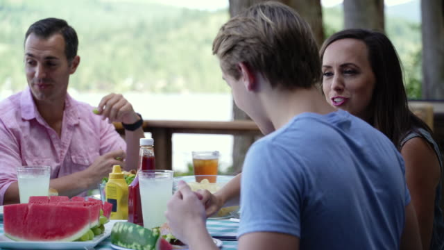 stockvideo's en b-roll-footage met family eating water melon at table by lake connaught, washington, usa. - familie met drie kinderen