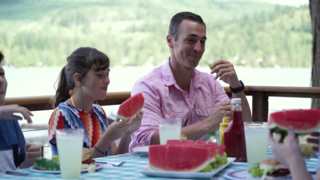 stockvideo's en b-roll-footage met family eating water melon at table by lakeside, lake connaught, washington, usa. - familie met drie kinderen