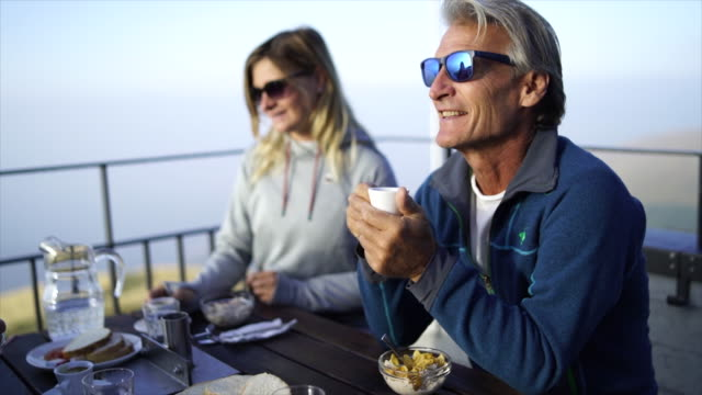 family eats breakfast on mountain hut terrace with view below - table top view video stock e b–roll