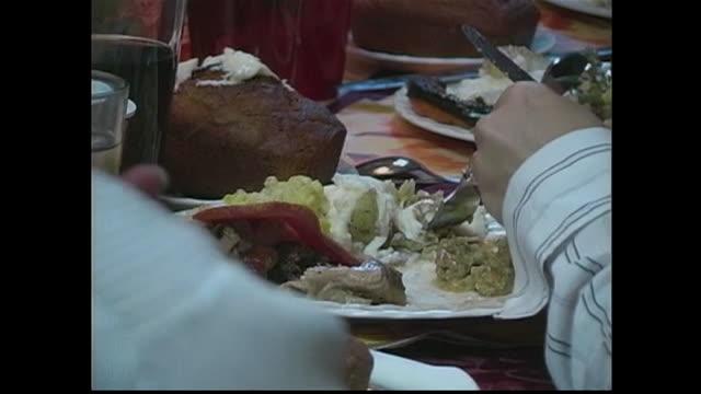 family eats thanksgiving dinner around a table. - マッシュポテト点の映像素材/bロール