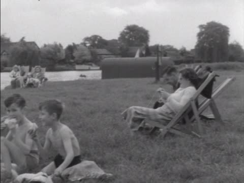 stockvideo's en b-roll-footage met a family enjoy a picnic alongside a river - rivieroever