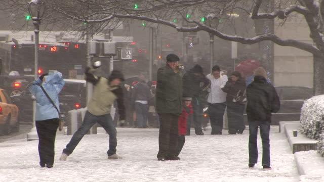 Family enjoy snowball fight 5th Avenue Manhattan