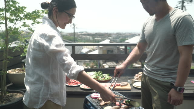 family enjoying a barbecue on the terrace - simple living stock videos & royalty-free footage