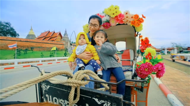 Family enjoying a horse drawn carriage ride in temple Phrathat Lampang Luang in Lampang, Thailand