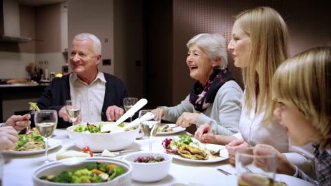 vídeos y material grabado en eventos de stock de familia disfrutando de una comida en la mesa de comedor y charlar - mesa de comedor