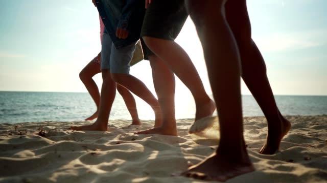 vidéos et rushes de famille appréciant la promenade de plage en vacances - quatre personnes