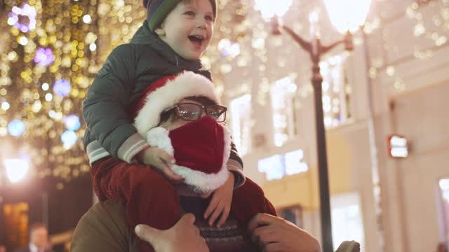 stockvideo's en b-roll-footage met familie die van de lichten van kerstmis bij een stadsstraat tijdens pandemie covid-19 geniet - feest en gedenkdagen