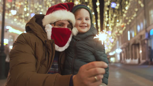 family enjoying christmas lights at a city street during covid-19 pandemic - christmas decoration stock videos & royalty-free footage