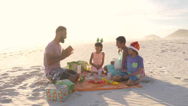 family enjoying christmas on the beach in summer - christmas meal stock videos & royalty-free footage