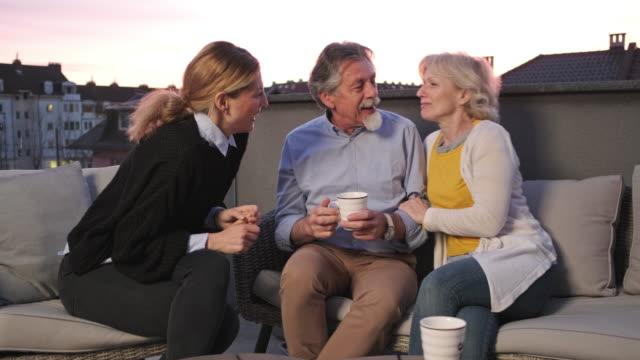 vidéos et rushes de famille appréciant le café et les collations sur une terrasse - en cas