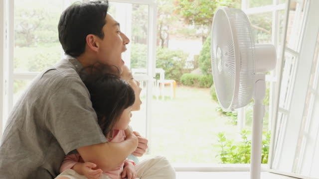 family enjoying cool air from electric fan in living room - stationary process plate stock videos & royalty-free footage