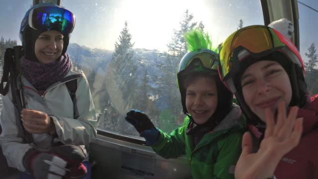 family enjoying gondola ski lift ride. - ski goggles stock videos & royalty-free footage