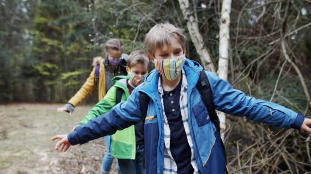 famiglia che si gode l'escursionismo nella foresta durante la pandemia di covid-19 - escursionismo video stock e b–roll