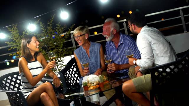 vídeos de stock, filmes e b-roll de família desfrutando quente noite de verão em uma varanda. - flute de champanha