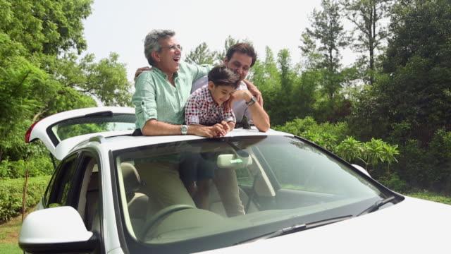 Family enjoying in the car sunroof