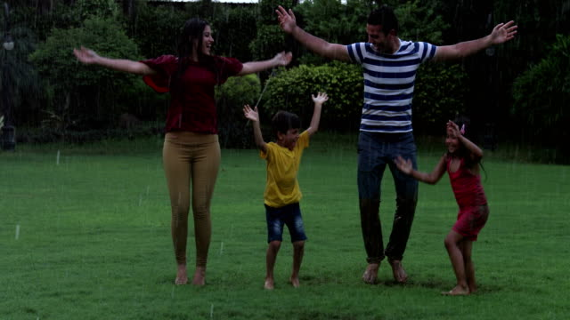 family enjoying in the rain season, delhi, india - arms outstretched stock videos and b-roll footage